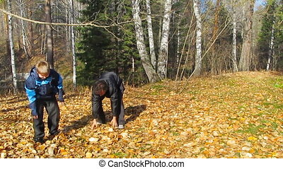 father and son playing with leaves