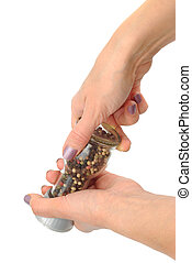 Peppering - Female hands holding pepper mill isolated on...