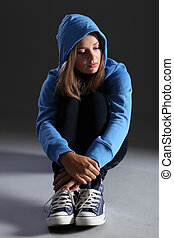 Blonde teenager girl alone and sad in blue hoodie - Hoodie...