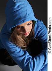 Sad teenager girl alone on floor in blue hoodie - Looking...