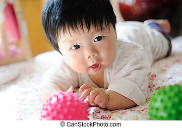Asian baby - An Asian baby lying on the bed
