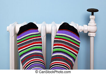 Warming feet on the radiator - Photo of a persons feet in...