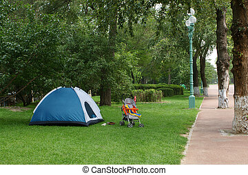 Blue camping tent in park, a horizontal picture