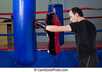 Boxer punching a sand bag with back hand