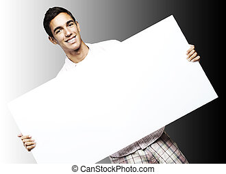 young man smiling and showing a big banner against a black...