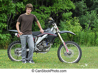 teenager with dirt bike - attractive teenage boy standing...