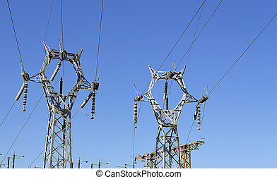 two pylons - two electricity pylons under a blue sky