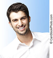 young man smiling - portrait of young man smiling over blue...