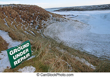ground under repair sign on a snow covered links golf course
