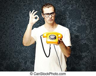 man with vintage telephone - young man holding a vintage...