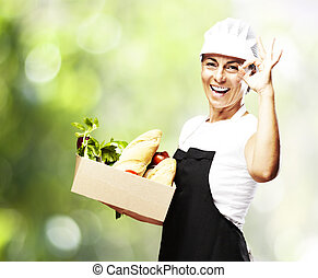 woman carrying food - portrait of middle aged woman carrying...