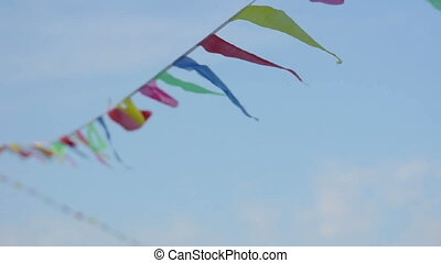 Multicolored striped triangular flags on a rope