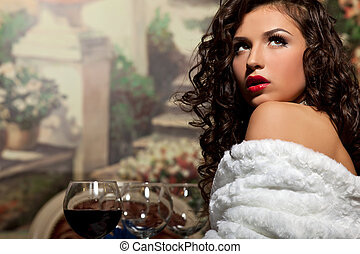 Sexy girl sit with wine in fur coat at evening look at light