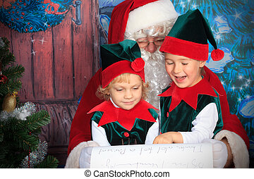 elves - Santa Claus sitting with two little cute elves over...