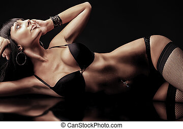 lingerie - Shot of a sexy woman in black lingerie over black...