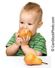 Cute little boy is biting pear