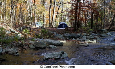 Tent Camping By Stream - Two tent set up camp next to a...