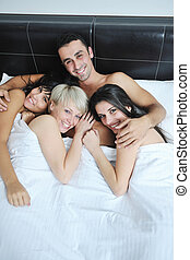 Young handsome man lying in bed with three girls -...