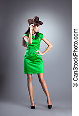 Young woman stand in green dress with hair hat
