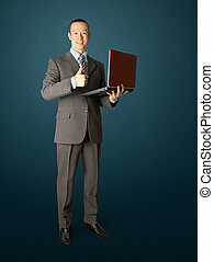 Full length portrait of businessman with laptop, showing...