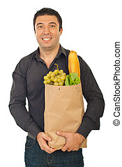 Cheerful man carrying shopping bag with food