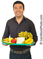 Happy man holding healthy food on plateau isolated on white...