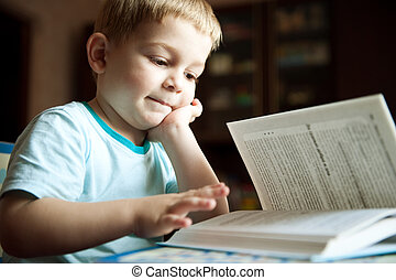 Boy reading book - Little boy is reading book at home