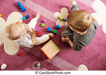 Brother and sister playing with toy blocks - A boy aged...