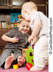 Brother and sister playing - A boy aged 3 and a girl aged 1...