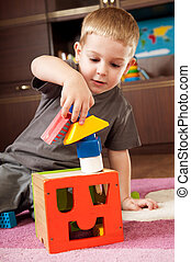 Little boy is building tower