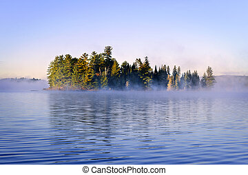 Island in lake with morning fog