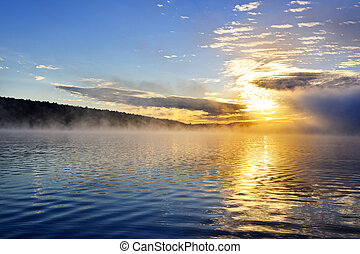 Sunrise on foggy lake - Sun rising over foggy lake in...