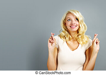 Happy woman crossing fingers - Smiling blonde caucasian...
