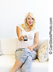 Woman on couch with tv remote