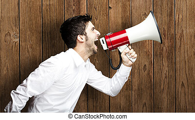 man shouting with megaphone - portrait of young man shouting...