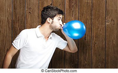 man blowing balloon - portrait of young man blowing balloon...