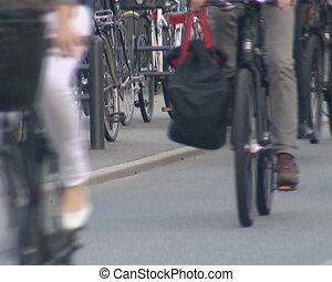 Many cyclists ride different bikes on dedicated bike path.