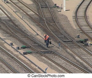 The man looking after the train tracks and a train running....