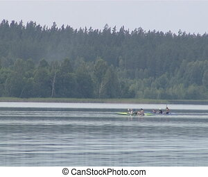 Canoes passing fast into lake