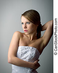 beautiful charming young woman in white corset on a gray...