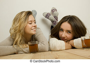 Two attractive friends drinking tea - Two attractive young...