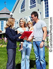 Happy family near new house. - Happy family with agent...