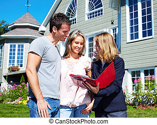 Happy family near new house - Happy family with agent...
