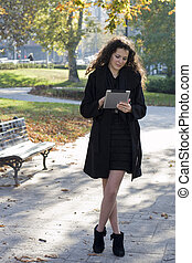 Young woman in the park with tablet pc