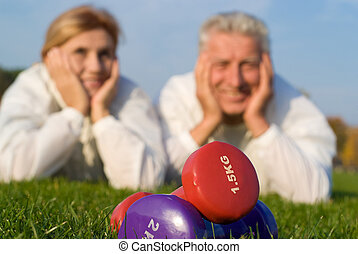 dumb bells and people - active old couple with dumb bells on...