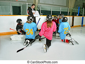 Hockey Coach with Players at Practice - A Hockey Coach at...