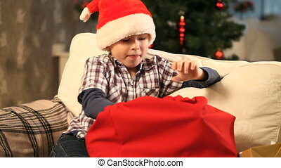 Boy with Christmas presents - Boy taking presents out of...