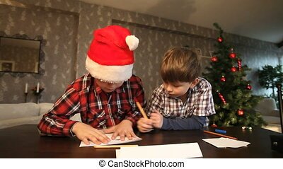 Sending Christmas letter - Two boys putting a letter to...