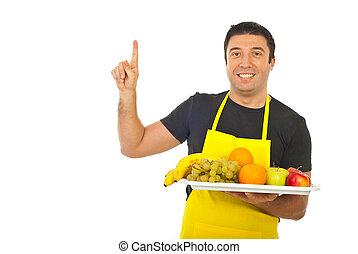 Smiling fruiterer pointing upwards - Smiling fruiterer...