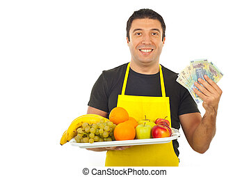 Happy greengrocer holding money and fresh fruits isolated on...